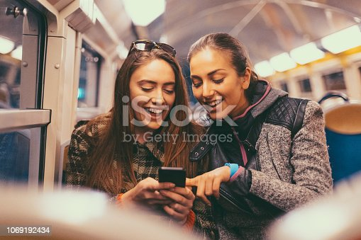 Beautiful girls using smartphone while traveling in the subway