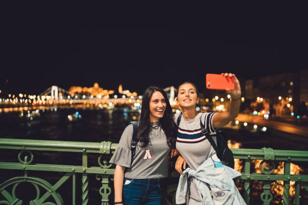 Girls taking selfie in Budapest Two girls hanging out in Budapest during the summer liberty bridge budapest stock pictures, royalty-free photos & images