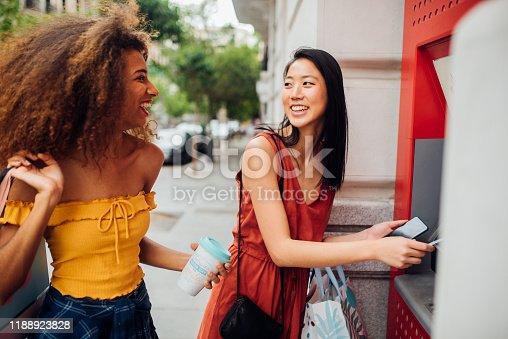 istock Girls taking the money from ATM machine 1188923828