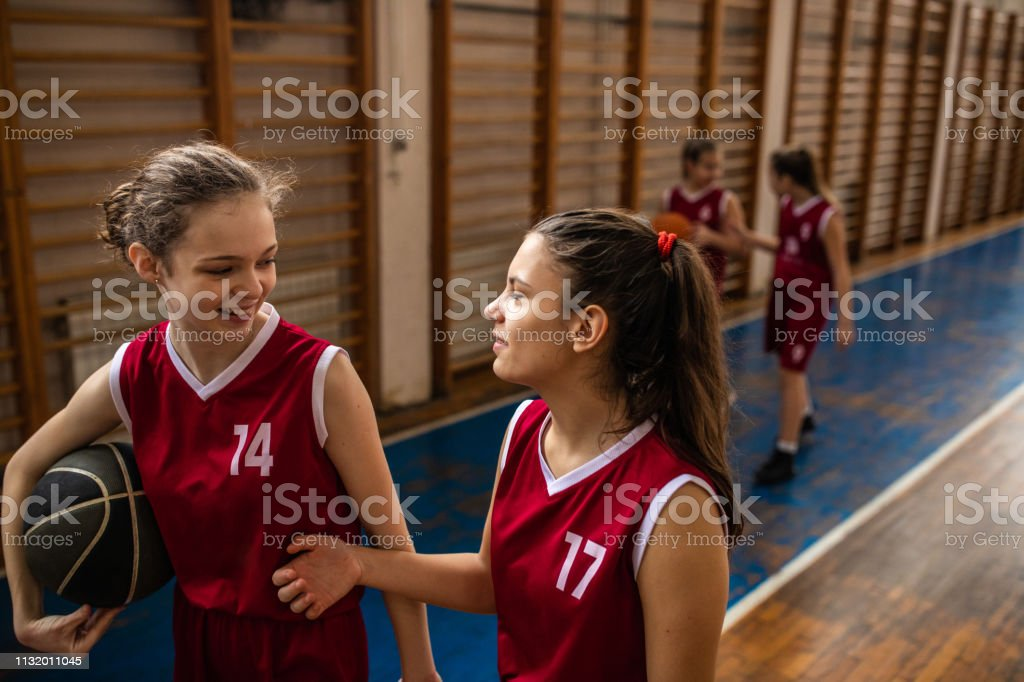 Cheerful teenage girls walking and holding basketball ball after...