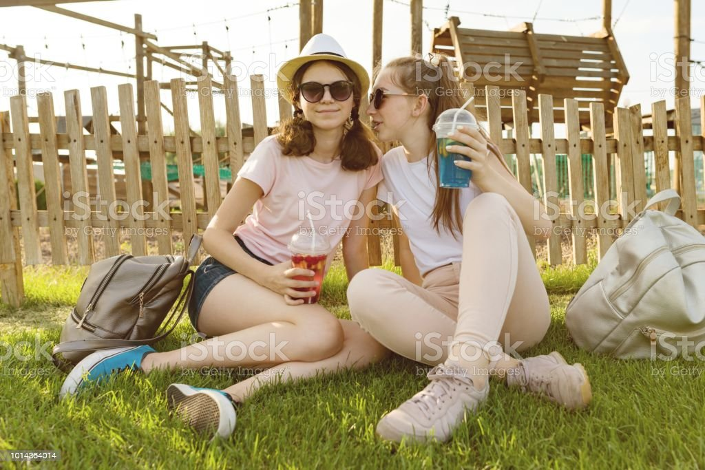 Girls teenagers 14,15 years have fun in a recreation and entertainment zone. They sit on the lawn, drink drinks, talk and secret. - foto stock