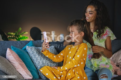 Side view of little girl recording a video with her smartphone while her mother brushes her hair in the living room.