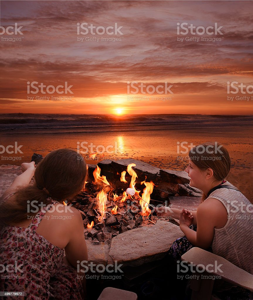 Girls toasting marshmallows outdoors.圖像檔