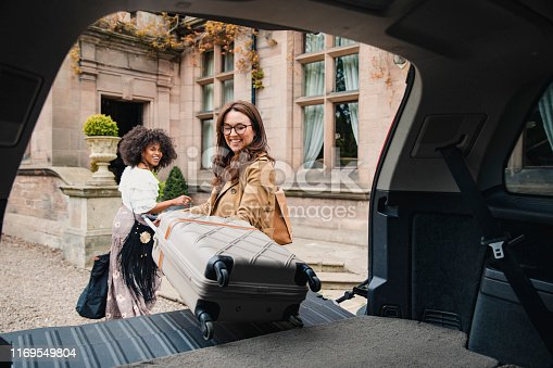 Two friends arrive at a luxury hotel where they are unloading their suitcases from their car trunk.