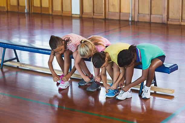 girls tying shoe laces in basketball court - sitzbank schuhe stock-fotos und bilder