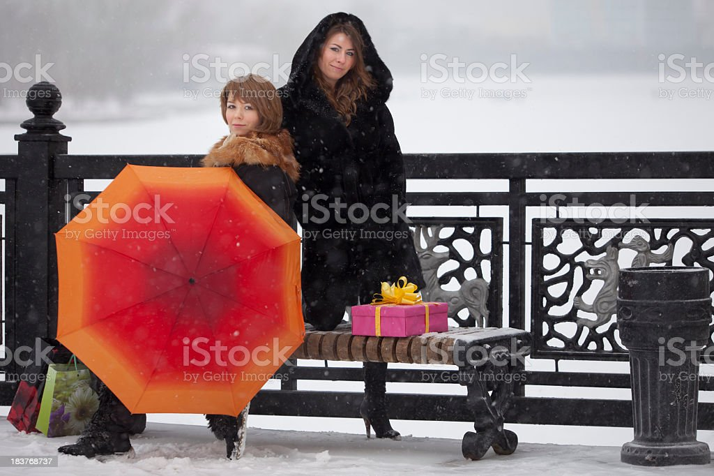 Girls: under snowing with orange umbrella and gifts stock photo