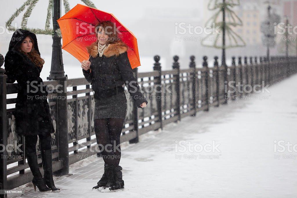 Girls: under snowing with orange umbrella stock photo