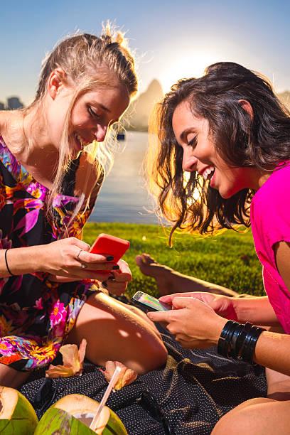 Girls using cell phone Girls using cell phone at Rio de Janeiro. lagoa rio de janeiro stock pictures, royalty-free photos & images