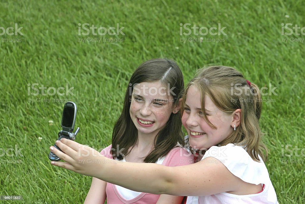 Girls Using Cell Phone to Take Picture royalty free stockfoto