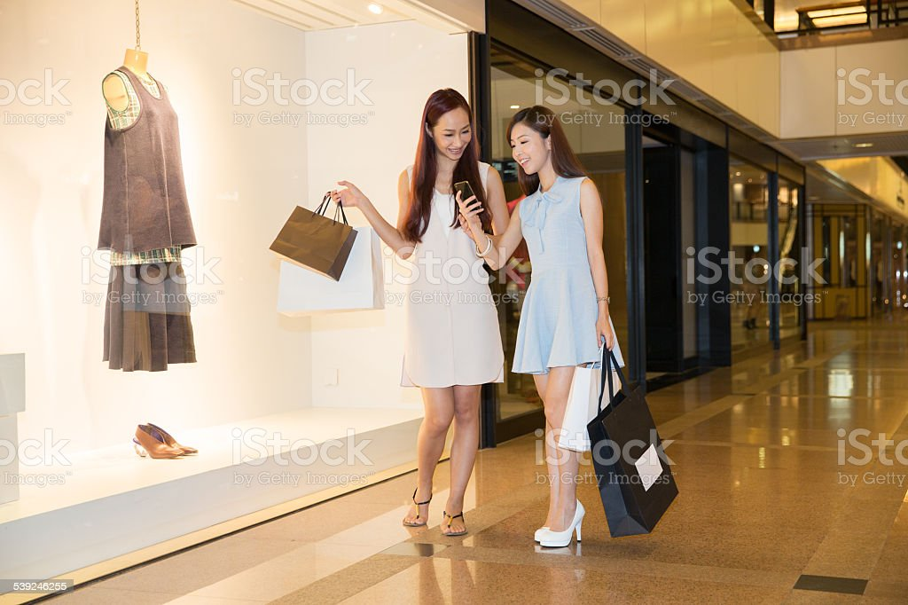 Girls using smart phone in a shopping mall stock photo