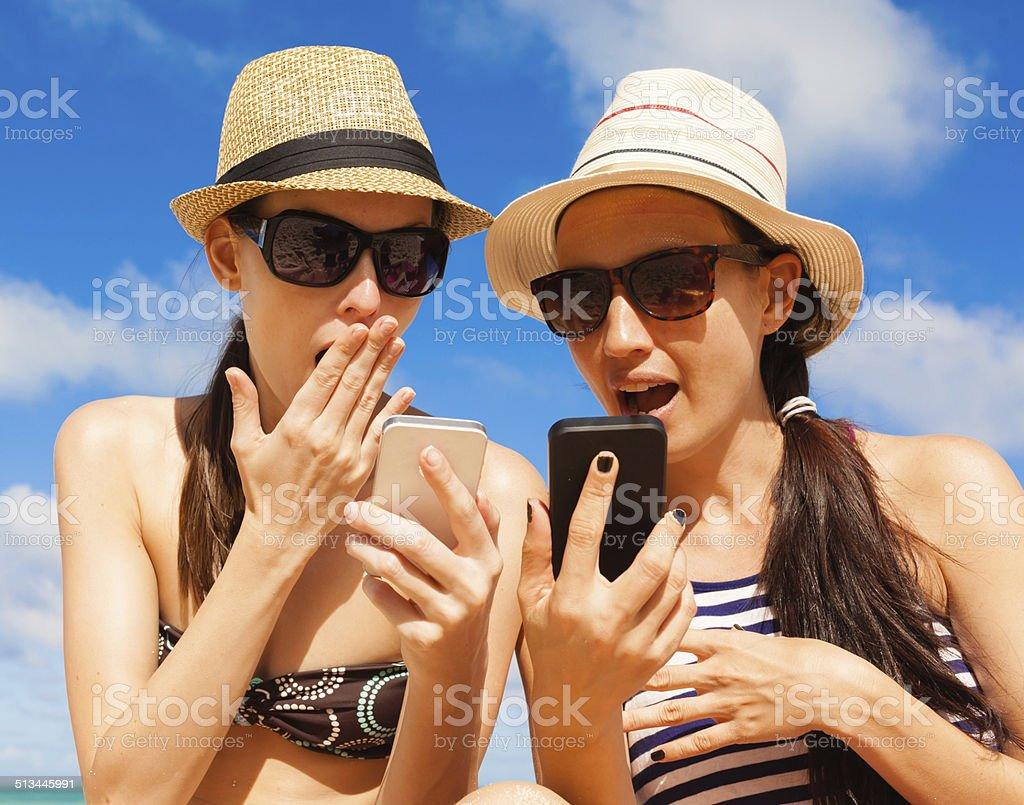 Girls using smart phone on the beach stock photo