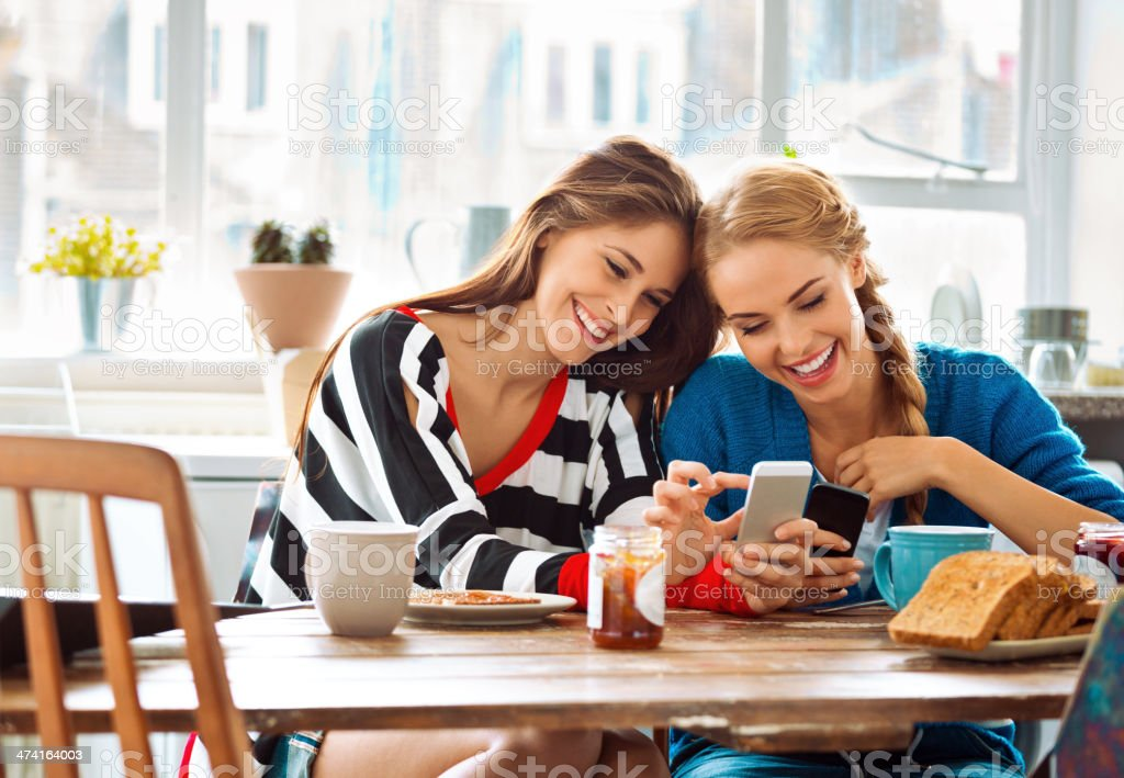 Girls using smart phones Two cheerful friends sitting at the kitchen table and using smart phones.  20-24 Years Stock Photo