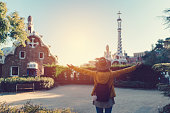 Rear view of young woman at park Guell with arms outstretched enjoying the beautiful city