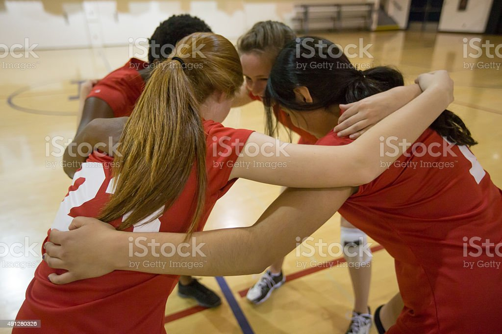 Girls volleyball players in team huddle stock photo