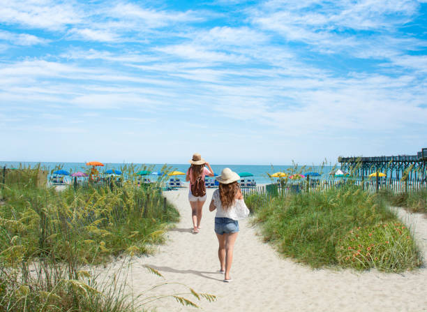 Girls waking on the beach on vacation in South Carolina. stock photo