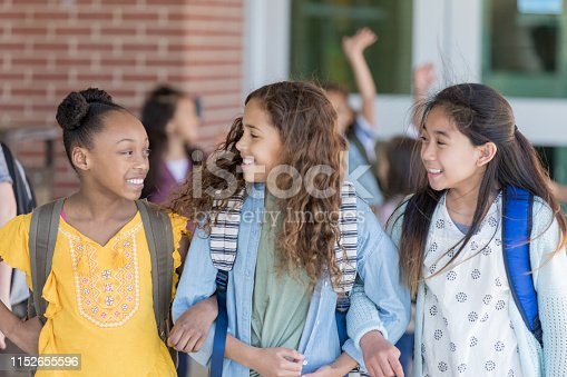 Three junior high female friends walk out of the school building arm in arm and talking together.