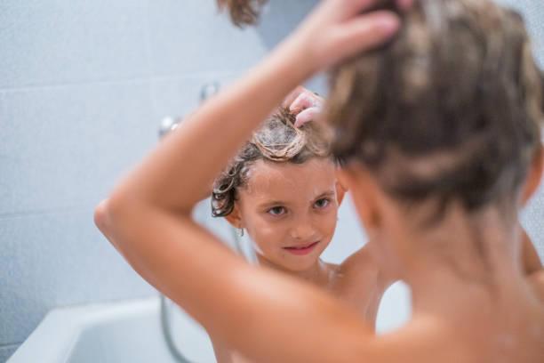 mädchen, die haare in der badewanne waschen - mädchen dusche stock-fotos und bilder