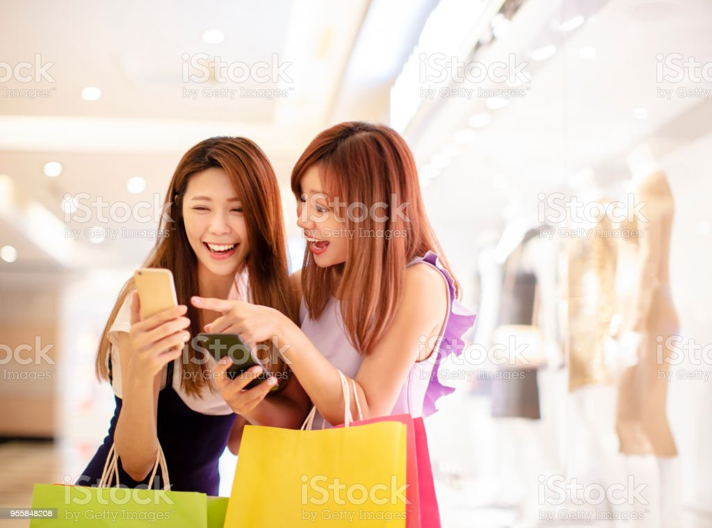girls watching phone and shopping in the mall stock photo