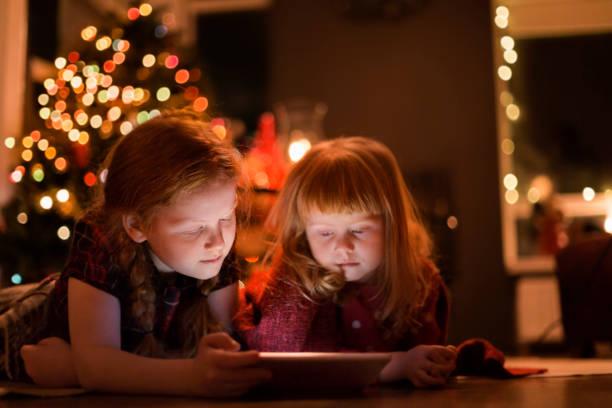 mädchen vor dem tablet-pc zu hause während weihnachten - kinder weihnachtsfilme stock-fotos und bilder