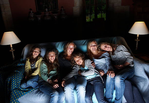 girls watching television on sofa - family watching tv stock photos and pictures