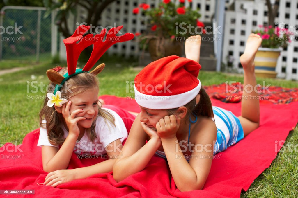 Girls (7-9) wearing Christmas hats, lying on blanket on lawn royalty free stockfoto