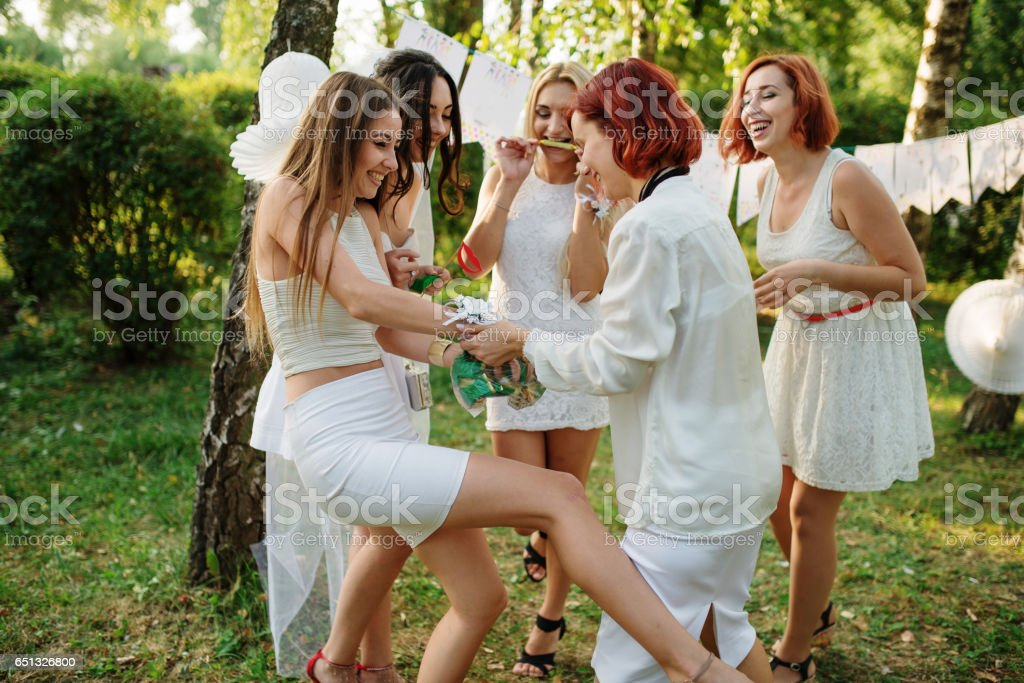 Girls wearing on white dresses having fun on hen party. stock photo