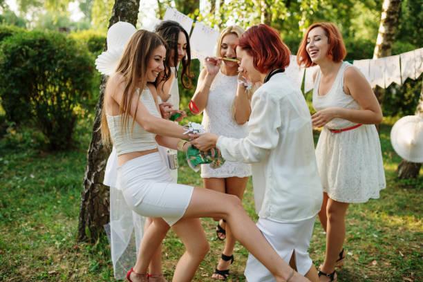 Girls wearing on white dresses having fun on hen party. - foto stock