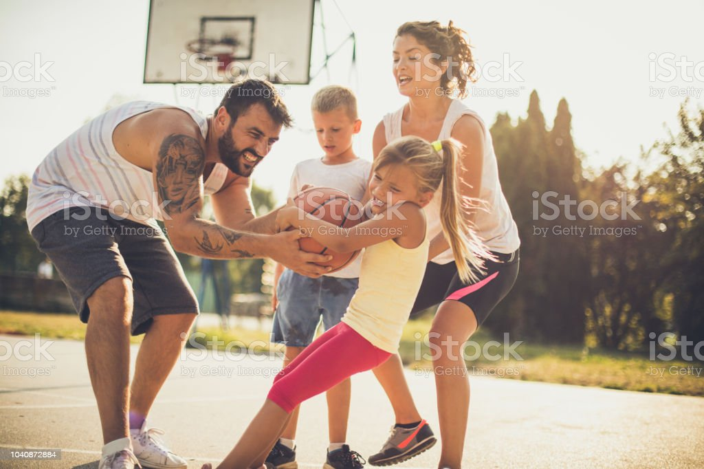 Girls will win. Happy family playing basketball. Moving activity....