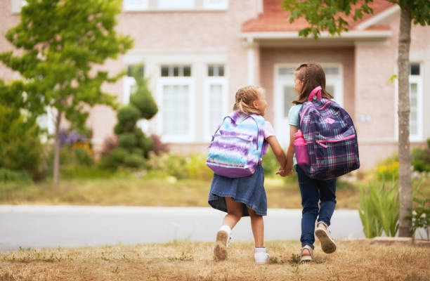 Girls with backpacks near building outdoors. stock photo