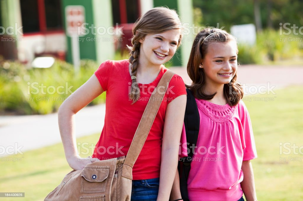 Girls with bookbags standing outside school royalty-free stock photo