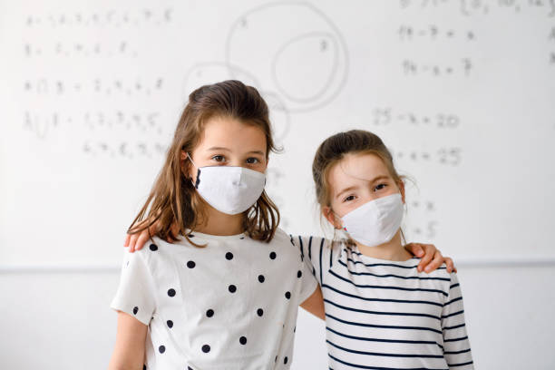 Girls with face mask back at school after covid-19 quarantine and lockdown. stock photo