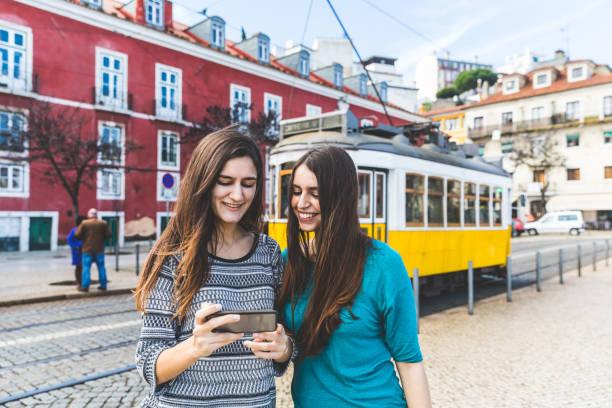 girls with smartphone in lisbon, tram on background - lissabon reise stock-fotos und bilder