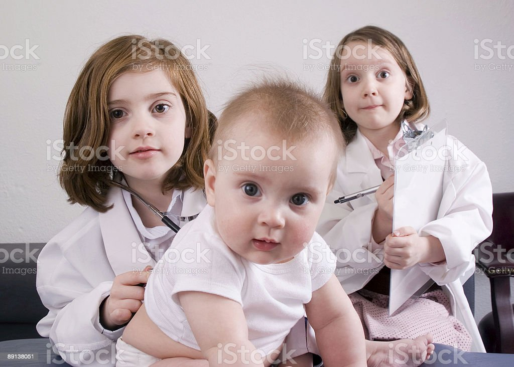 Girls with stethoscope playing doctor examine their brother stock photo