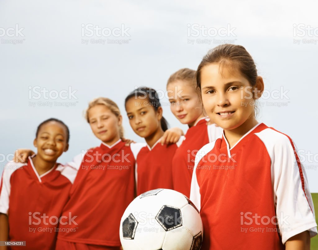 Girls with their captain holding a soccer ball royalty-free stock photo