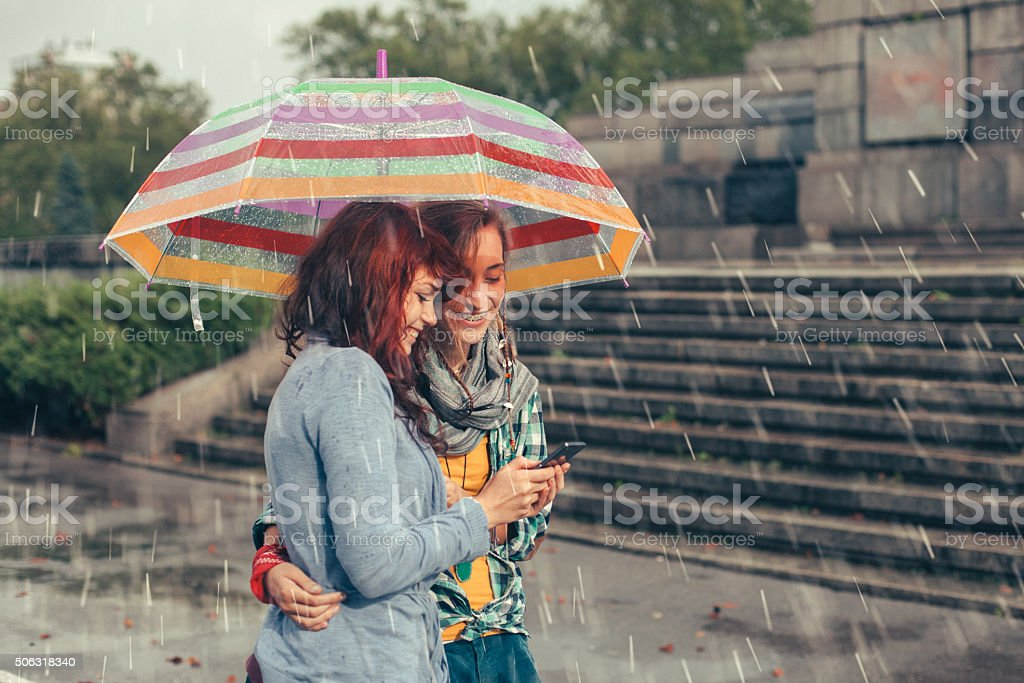 Girls with umbrella on a rainy day stock photo