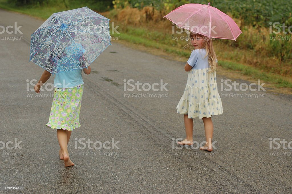 Girls with Umbrellas Walking in the Rain stock photo