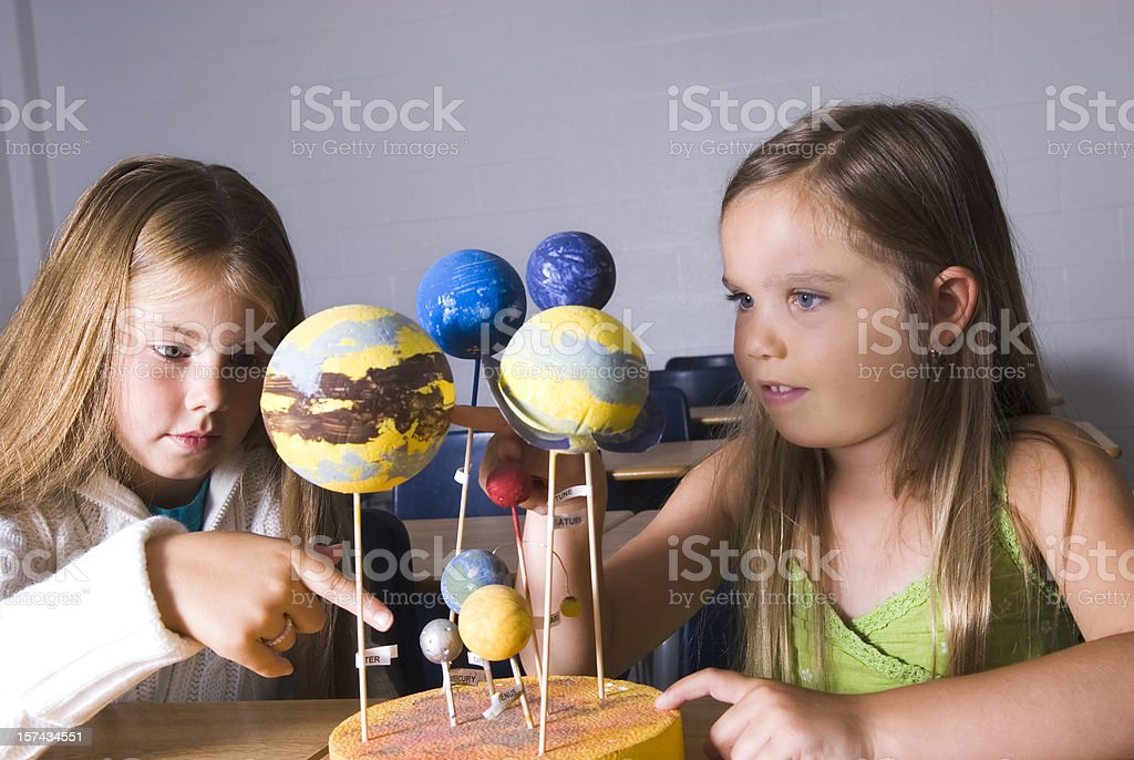 Girls working with space models in the classroom royalty-free stock photo