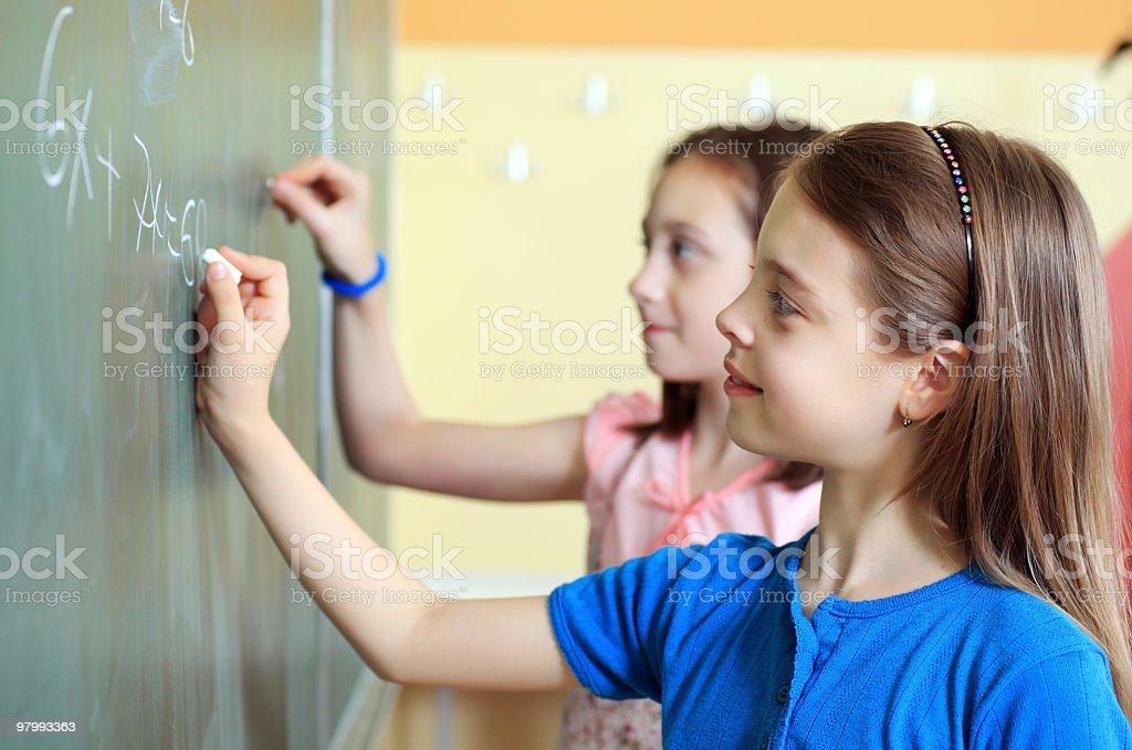 Girls writing math using chalk on green blackboard. royalty free stockfoto
