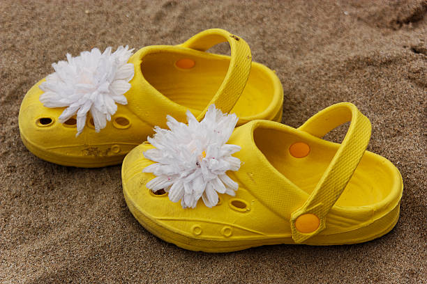 girls yellow beach shoes on the sand stock photo