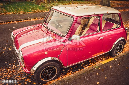 Classic mini car in pink colour parked at the street in Autumn.