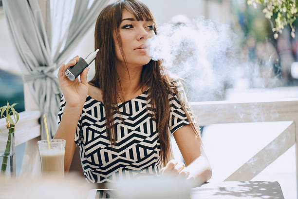 girn in cafe with E-Cigarette stock photo