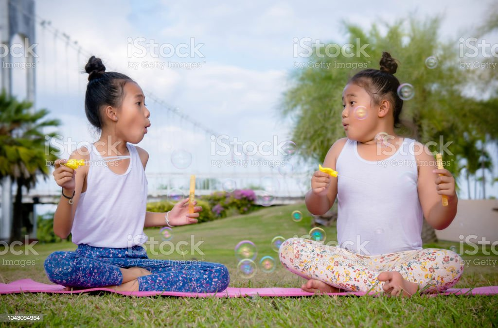 Girs Play And Enjoy Activities Blow Bubbles In The Park Friendship