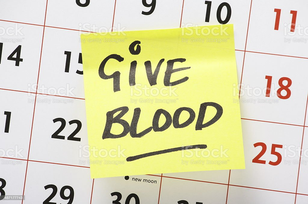 Give Blood written on a yellow note on a calendar stock photo