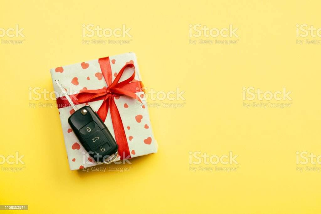 Give gift car key concept top view. Present box with red ribbon bow,...