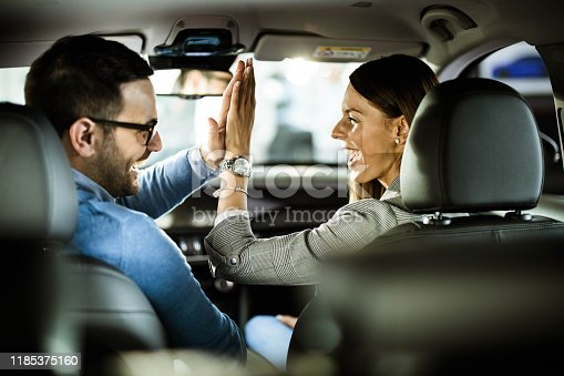 Young happy couple sitting inside of their new car and giving each other high-five.