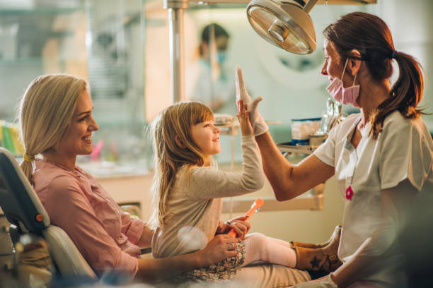 Give me high-five, you were great at dental exam! Happy girl with her mother giving high five to a dentist after medical exam at dentist's office. dentist stock pictures, royalty-free photos & images
