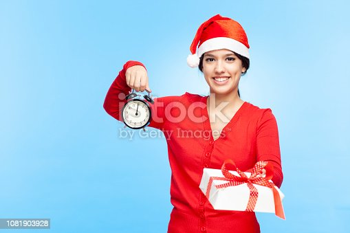A happy young woman in Santa hat giving a present, showing alarm clock on 12 AM / PM. New year / Christmas concept. Studio shot isolated on blue.