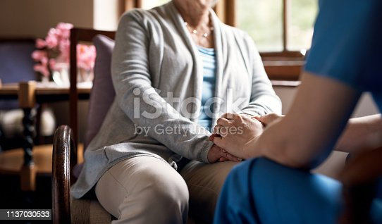 Cropped shot of a nurse holding hands with an elderly woman in a retirement home