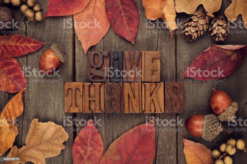 Give Thanks letterpress with frame of autumn leaves over wood stock photo