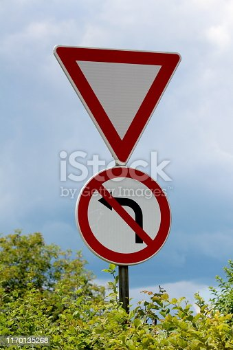 Give way and no left turn red and white signs mounted on strong metal pole surrounded with dense leaves on cloudy stormy blue sky background
